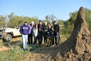 Students are pictured with a giant termite mound in South Africa.