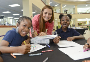 The photo features from left to right Montlieu Academy of Technology student Autum Kennedy, HPU student Nicole Karlesky and Montlieu Academy of Technology student Kaleigh Anderson writing letters to U.S. troops.