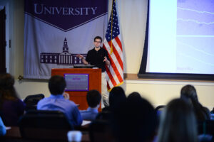 """HPU student Ryan Casey presenting his research, """"The Effects of ATM-Mediated Reactive Oxygen Species Generation on Cell Migration,"""" at SuRPS."""