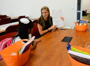 HPU graduate student Sarah Robinette leading Montlieu Academy third grader Daisy Castelan in a reading activity.
