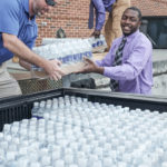 Shannon Brewer from Richard Childress Racing (left) and HPU employees Tim Judd (back) and Jason Davis (right) load HPU's 1,000-pound water donation onto a truck.