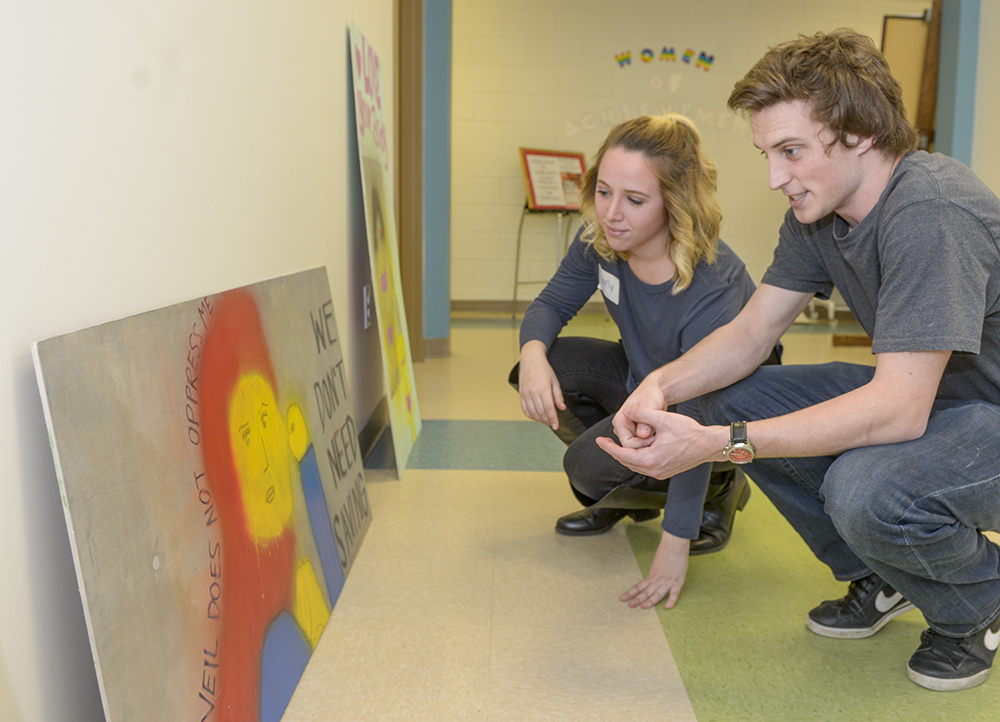 HPU student Carly Delengowski (left) and community member Tyler Moncourtois admire the graffiti art created by HPU students.