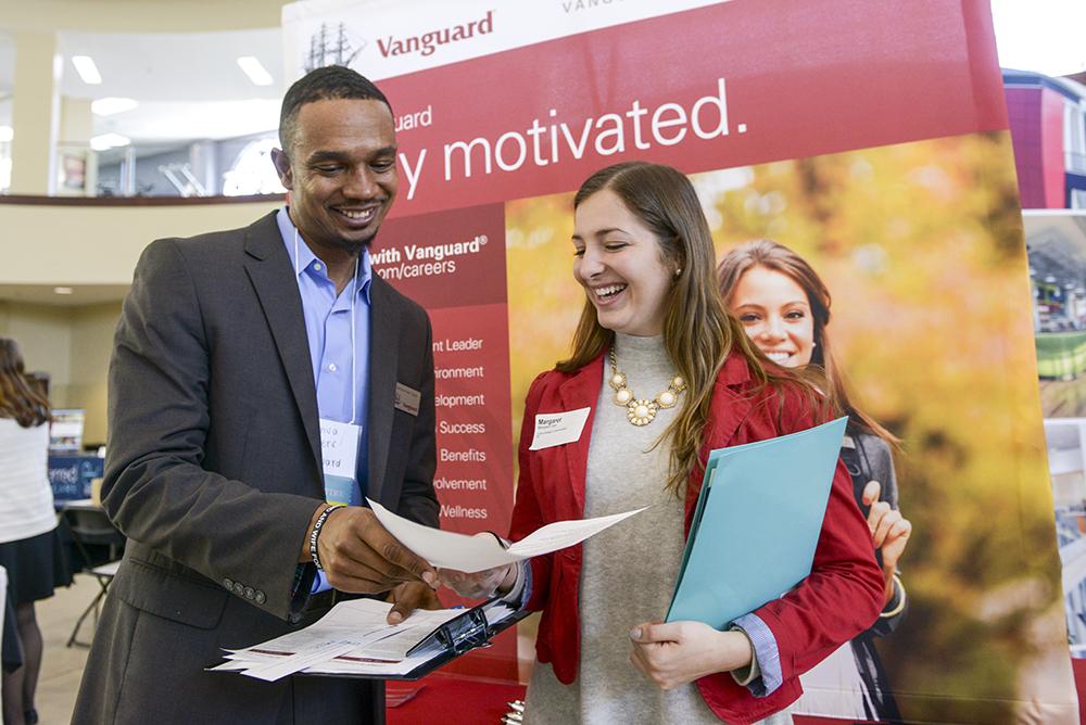 Joshua Peters (left), employee at Vanguard, receives HPU student Margaret Cart's resume.