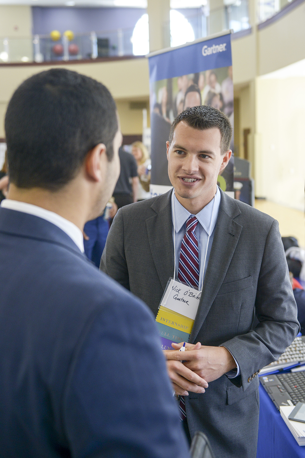 Nick O'Brien, HPU alumnus and account executive at Gartner Consulting, speaks with HPU students at the Career and Internship Expo today.