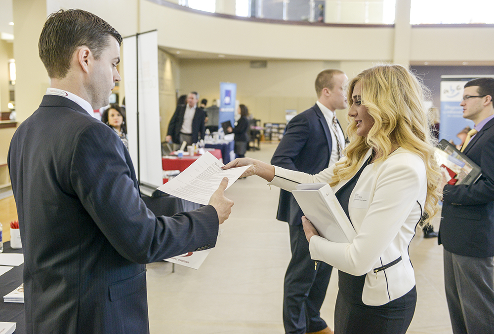 Brett Alter (left), corporate recruiter for Insight Global, speaks with HPU student Alex Saunders at the expo.