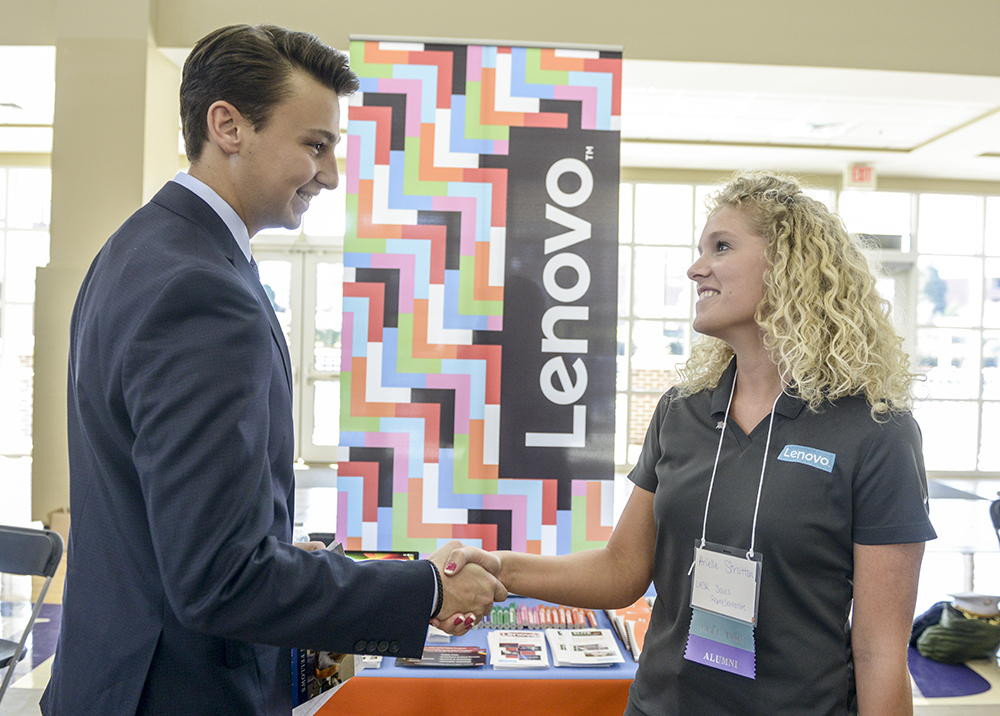 HPU student Austin Decker (left) speaks with Arielle Stratton, HPU alumna and sales representative at Lenovo, at the expo.