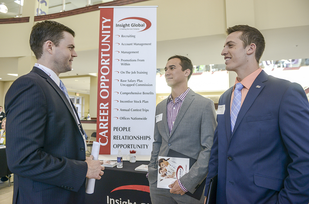 Brett Alter (left), corporate recruiter for Insight Global, speaks with HPU students Michael Hennessey (center) and Christopher Clare, about job opportunities at Insight Global.